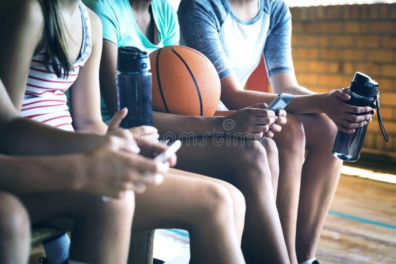 Дети средней школы используя мобильный телефон пока ослабляющ стоковые фото