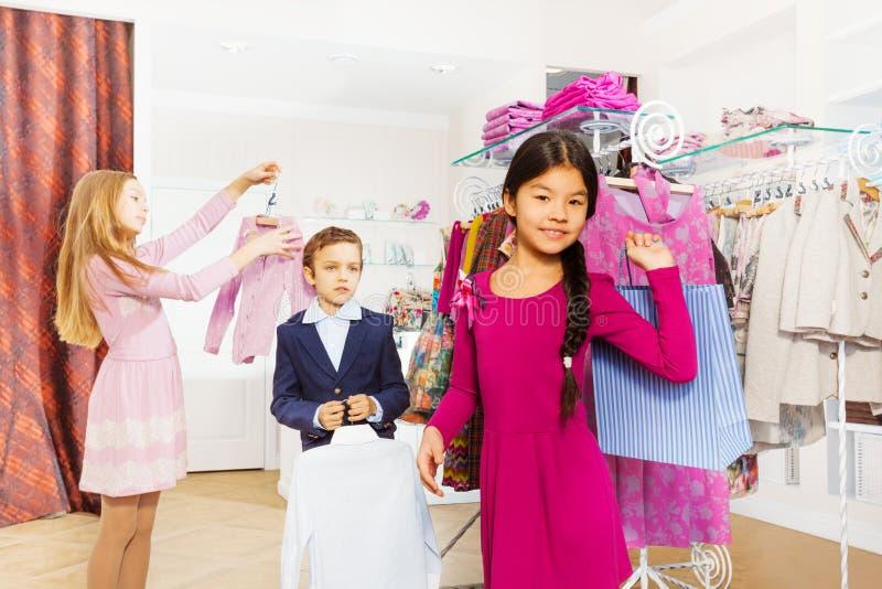 Дети стоя совместно в магазине одежды стоковое фото rf