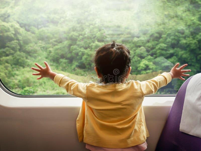 Дети счастливых и Ecxited путешествуя поездом Девушка 2 года старая стоковая фотография