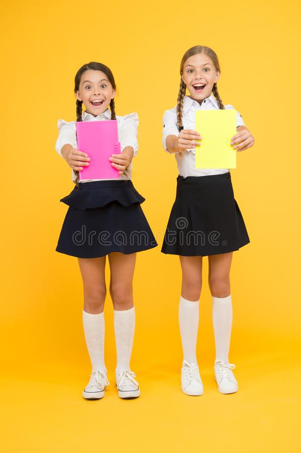Дети с дневниками школы для примечаний Милые школьницы держа книги урока Ребята школьного возраста учат книги чтения r стоковое фото