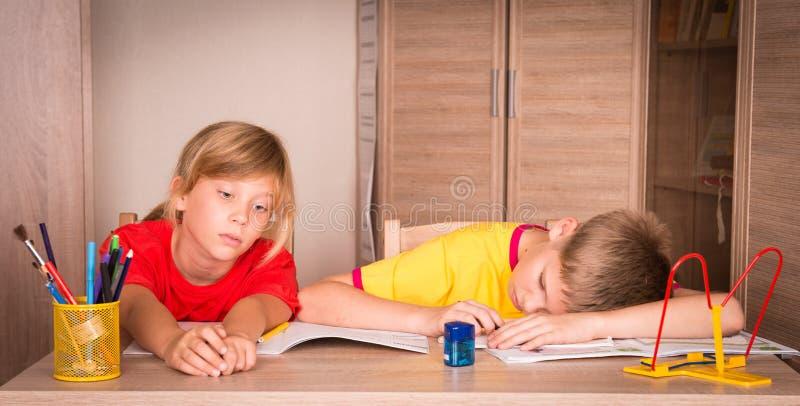 Дети с затруднениями в учебе Утомленный мальчик и пробуренная девушка делают стоковые изображения