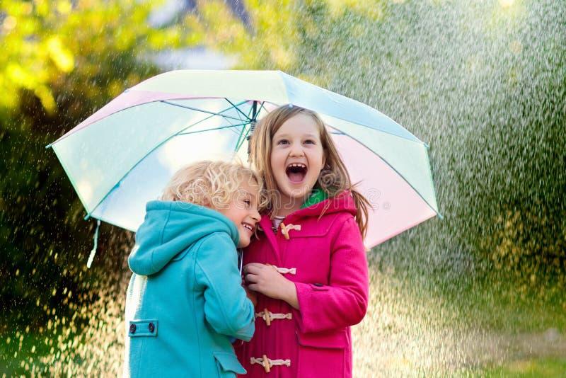 Дети с зонтиком играя в дожде ливня осени стоковое фото