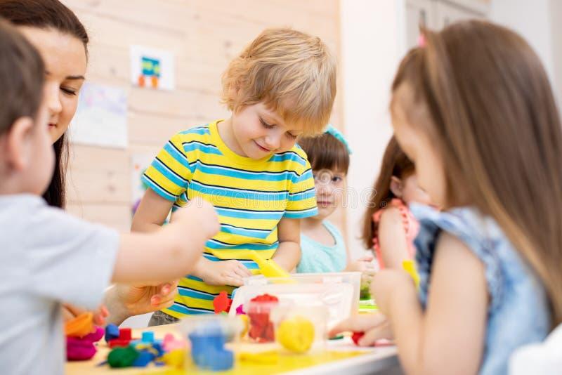 Дети с игрушкой глины игры учителя красочной в daycare стоковая фотография