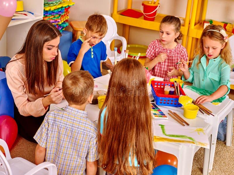 Дети с картиной женщины учителя на бумаге в детском саде стоковые изображения