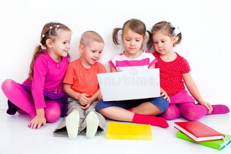 Дети с компьтер-книжкой стоковое изображение
