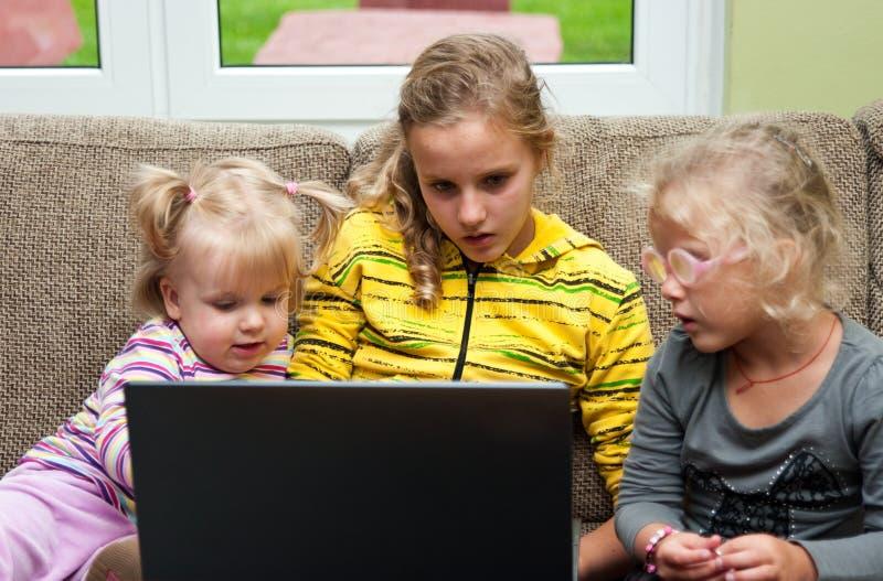 Дети с компьтер-книжкой стоковая фотография