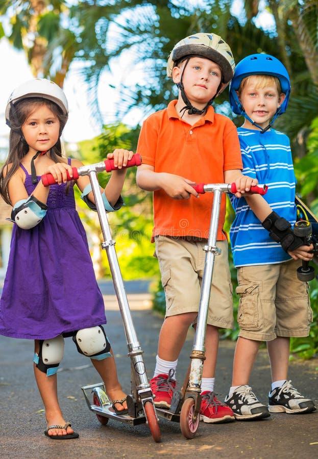 Дети с досками и самокатами конька стоковое изображение