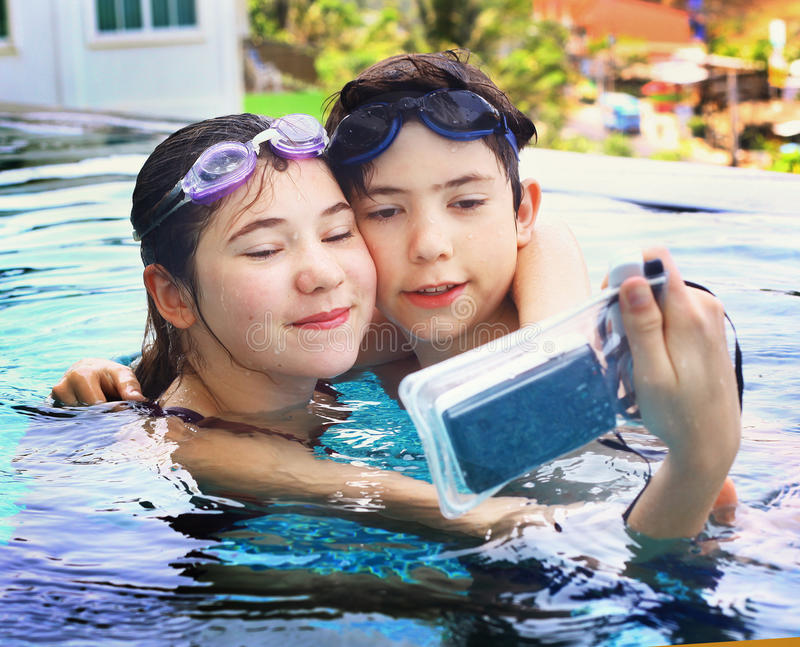 Дети с подводной камерой в бассейне стоковая фотография