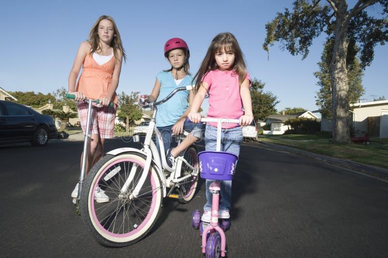 Дети с самокатами и велосипедом стоковые изображения