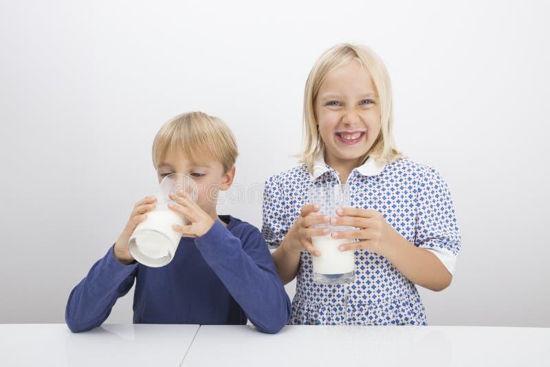 Дети с стеклами молока на таблице стоковые фотографии rf