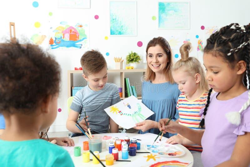 Дети с учительницей на крася уроке стоковое фото