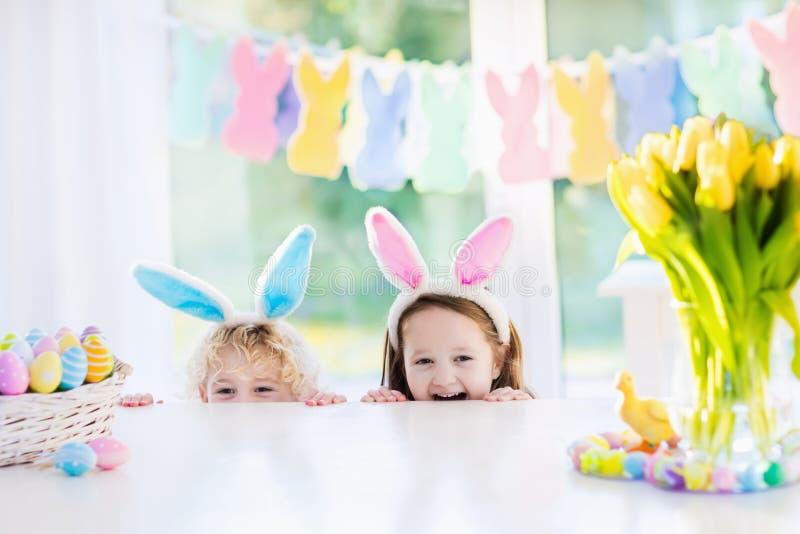 Дети с ушами зайчика на пасхальном яйце охотятся стоковое фото rf