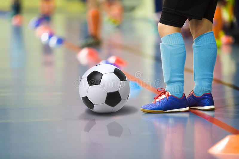 Дети тренируя спортзал футбола futsal крытый Молодой мальчик с футбольным мячом тренируя крытый футбол Маленький игрок в свете -  стоковое фото
