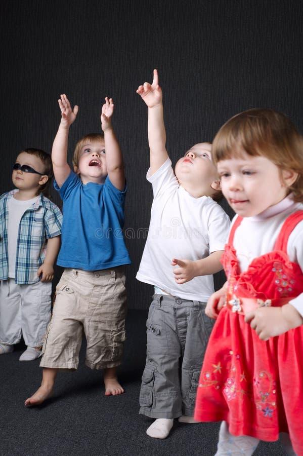 Дети указывая вверх на темную предпосылку стоковое изображение