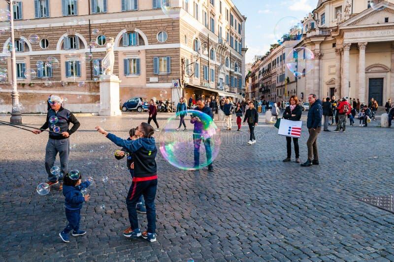 Дети улавливая и дуя пузыри мыла летая на Аркаду del Popolo, квадрат людей в Риме вполне людей, туристов и locals с стоковое фото