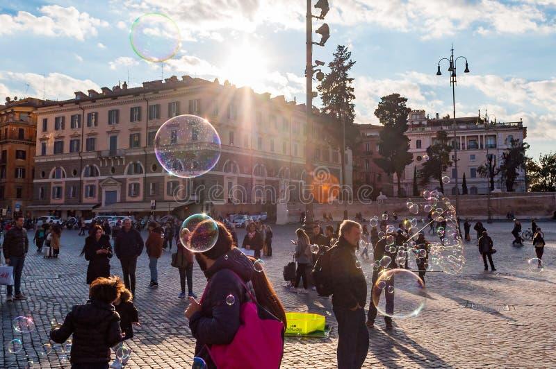 Дети улавливая и дуя пузыри мыла летая на Аркаду del Popolo, квадрат людей в Риме вполне людей, туристов и locals с стоковые фотографии rf