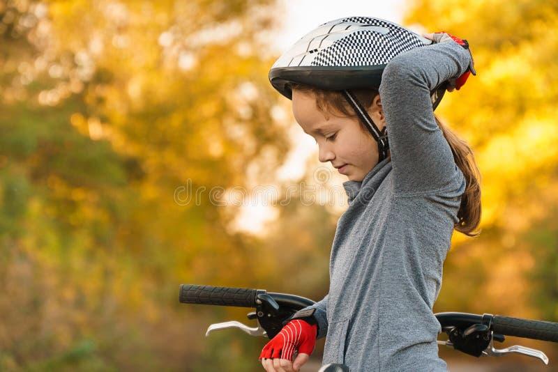 Дети уча управлять велосипедом на подъездной дороге снаружи Маленькие девочки ехать велосипеды на дороге асфальта в шлемах города стоковая фотография