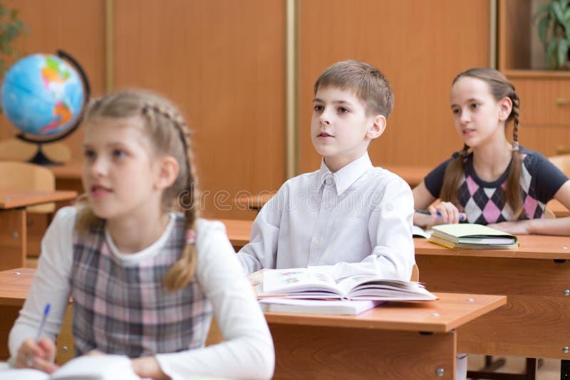 Дети школы на столе в уроке начальной школы стоковые фотографии rf