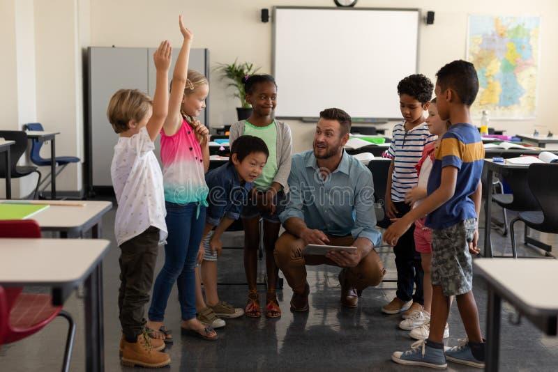 Дети школы поднимая руки пока преподавательство учителя стоковые изображения rf