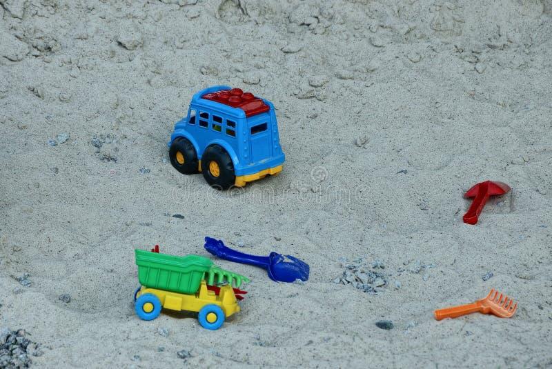 Дети ` s покрасило пластичные игрушки лежат на песке в ящике с песком стоковые изображения rf