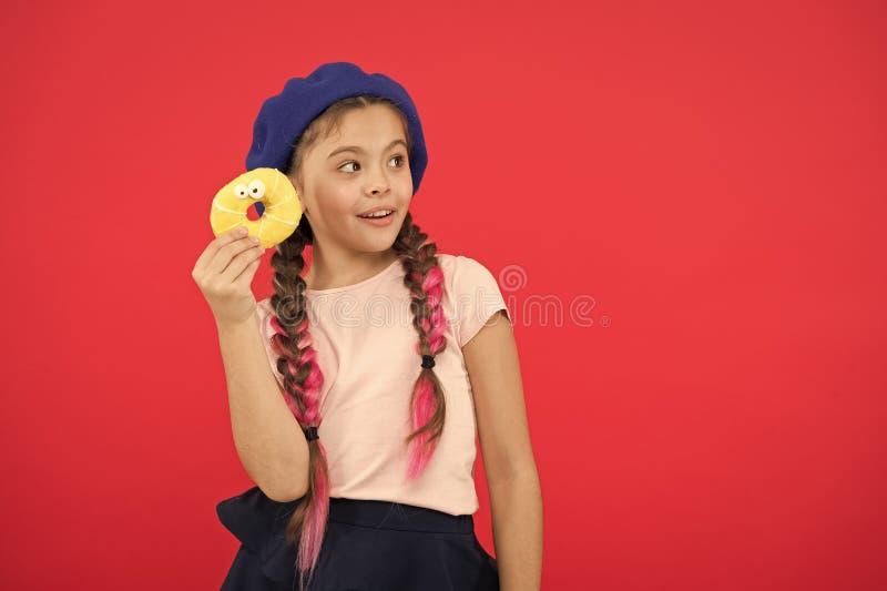 Детка-игрушка готова съесть пончик Концепция магазина сладостей и булочной Дети - огромные поклонники печеных пончиков Невозможно стоковое изображение
