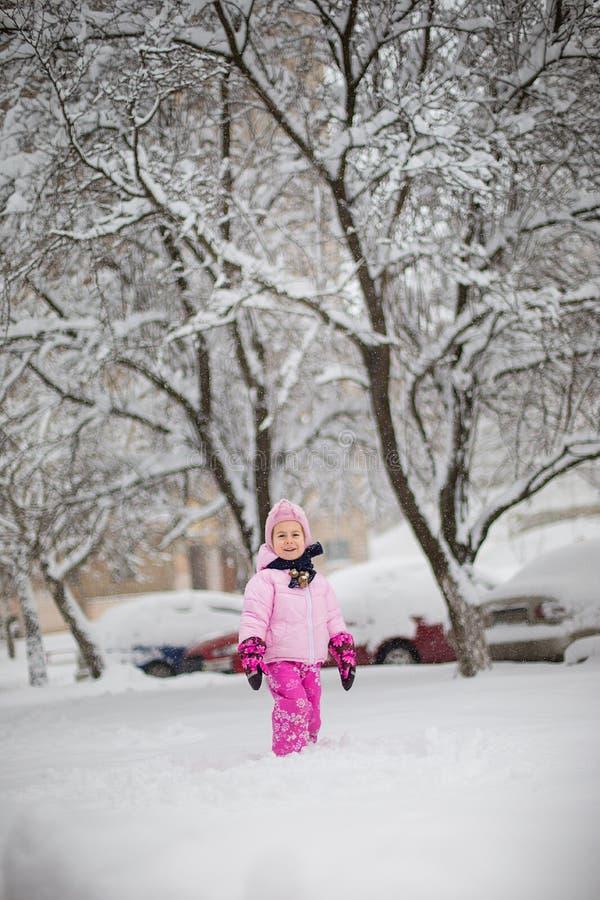 Детские игры со снегом в зиме Маленькая девочка в яркой куртке и связанной шляпе, улавливает снежинки в парке зимы для стоковое фото rf