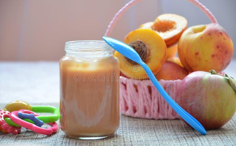 Детское питание, плодоовощ помятый в стеклянном опарнике, персик младенца, красивые персики в корзине, игрушка ` s детей Apple стоковое фото