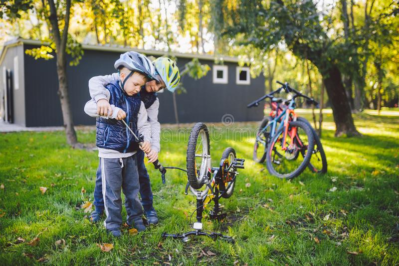 2 дет, более старых мальчики и младший брат уча велосипед ремонта 2 брать парней в шлемах и одиночных одеждах используют инструме стоковые фото