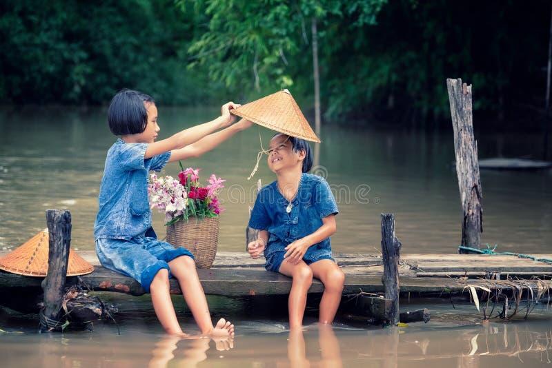2 дет девушки сидя и играя вода совместно на деревянном мосте над болотом, азиатскими детьми играя воду стоковые изображения rf