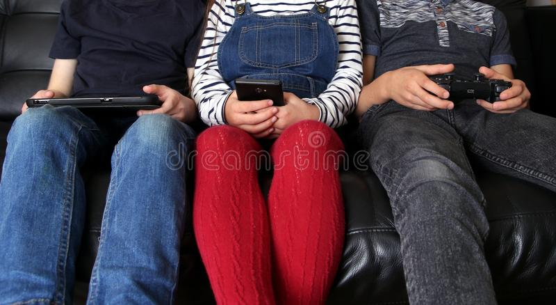 3 дет играя с электронными устройствами - таблеткой, smartph стоковое изображение