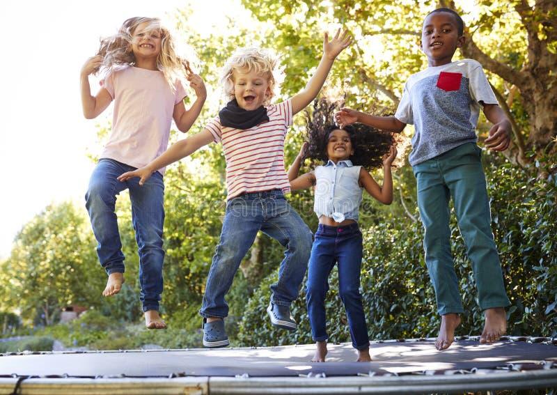 4 дет имея потеху совместно на батуте в саде стоковое фото