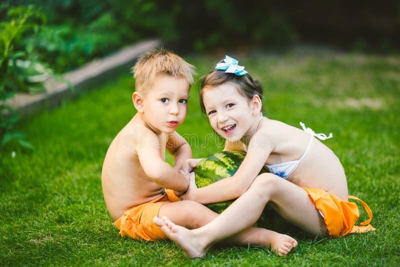 2 дет, кавказский брат и сестра, сидя на зеленой траве в задворк дома и обнимая большой вкусный сладкий арбуз стоковая фотография rf