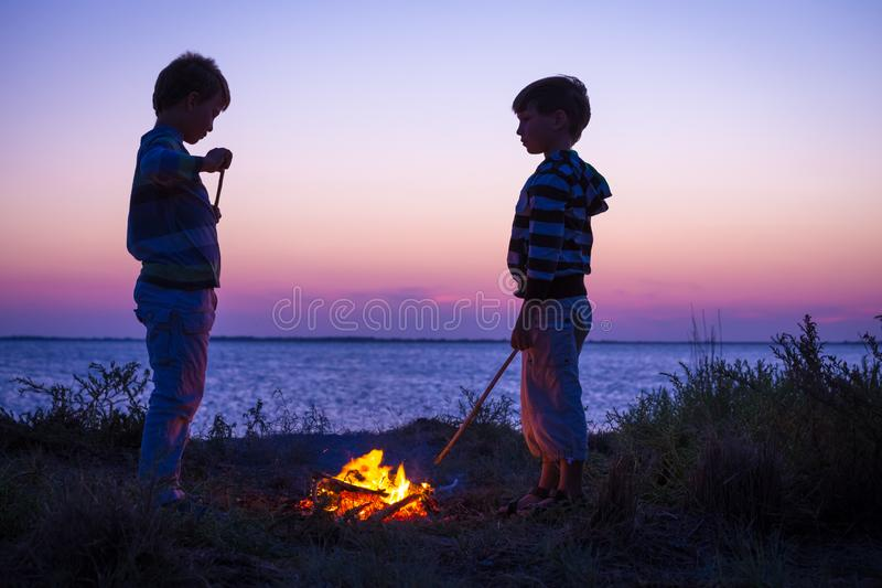 2 дет на пляже с лагерным костером на заходе солнца стоковая фотография
