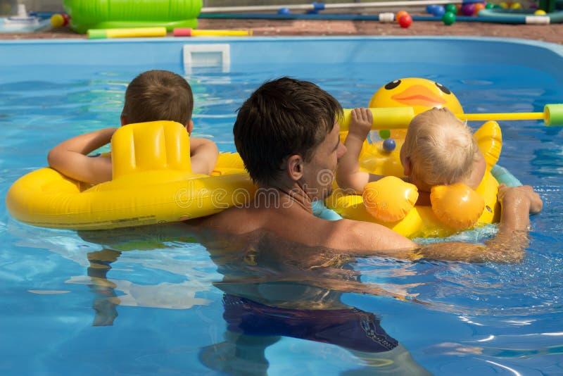 2 дет с тренером, с папой учат поплавать в бассейне, виде сзади заботы, каникулы раздувные круги lifebuoy стоковая фотография rf
