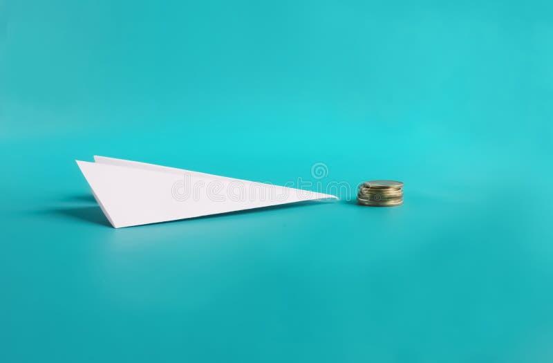 Дешевая концепция низкой цены полета Бумажные самолет и монетки стоковое изображение