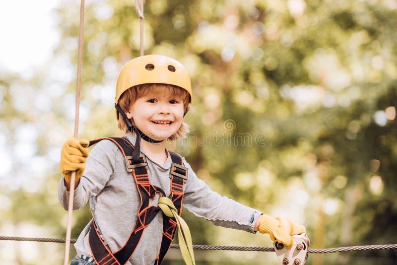 Деятельности при лета детей Парк натянутой проволоки приключения взбираясь Милая игра ребенка Пеший туризм в девушке парка верево стоковые фотографии rf