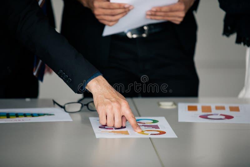 Деятельность и пункт бизнесменов на документах диаграммы и анализа диаграммы финансовых на таблице офиса стоковая фотография rf