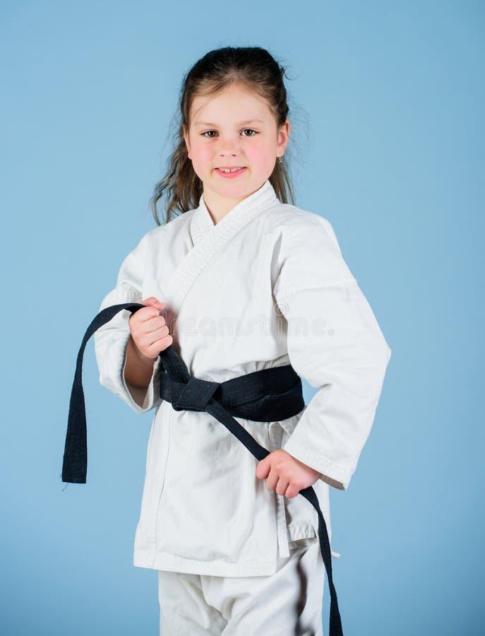 Деятельность и спорт Сильный и уверенный ребенк Ребенок девушки маленький в белом кимоно с поясом Боец карате готовый для боя стоковое изображение rf