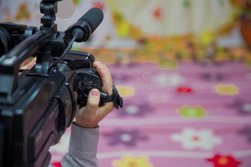 Деятельность камкордера оператора видеокамеры управлением руки с его оборудованием на открытом воздухе с запачканной предпосылкой стоковая фотография rf