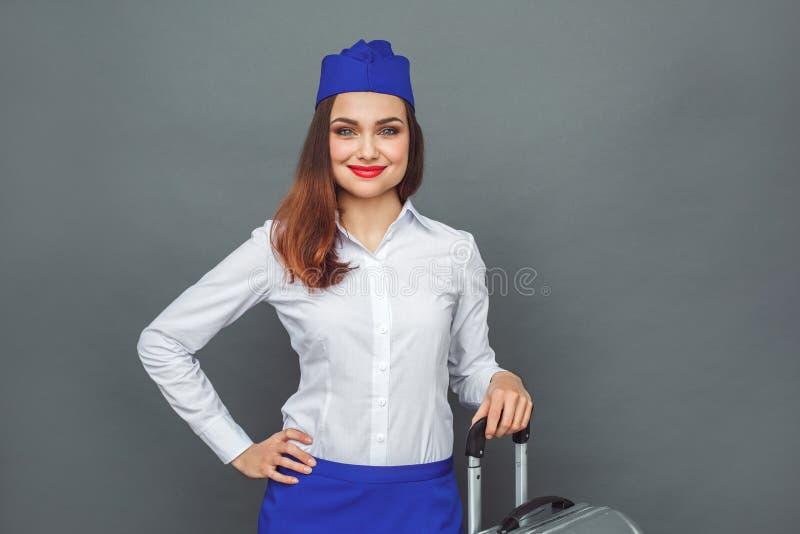 деятельность людей занятия трудной работы дела профессиональная Положение Stewardess на сером цвете с усмехаться чемодана радостн стоковое изображение rf