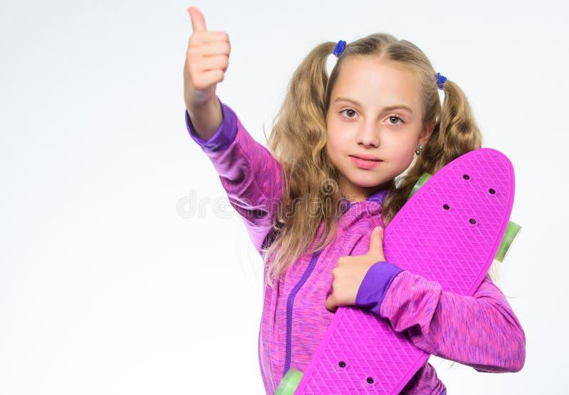 Деятельность при спорта потеха имея скейтборда Я имею доску пенни Небольшая девушка после ехать маленькая девочка с пурпурным кон стоковая фотография