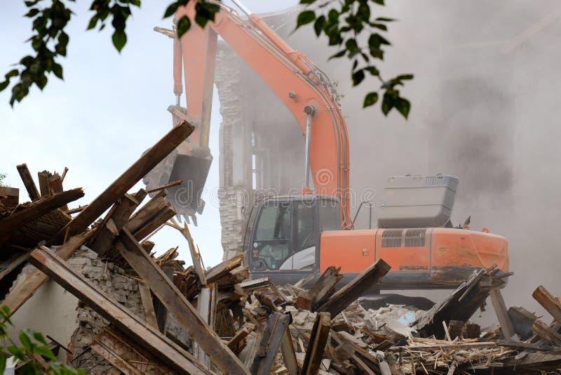 Деятельность экскаватора в руинах разрушенных зданий, упаденного здания и землекопа стоковое изображение