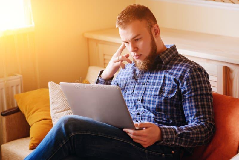 Деятельность молодого человека поглощенная на компьтер-книжке дома стоковое фото
