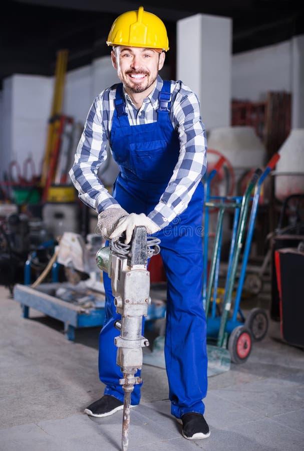 Деятеля практикуя его искусства с пневматическим сверлом на worksh стоковая фотография