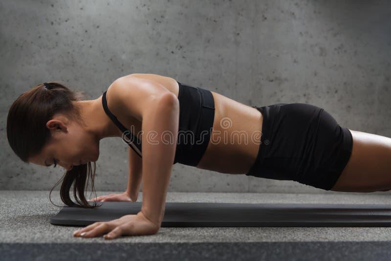Делать женщины нажим-поднимает в спортзале стоковое изображение