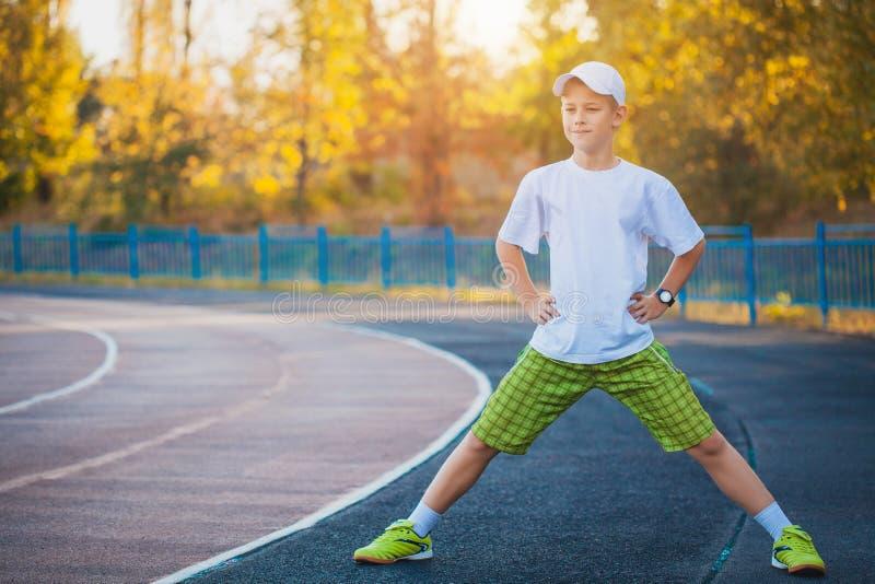 Делать мальчика предназначенный для подростков резвится тренировки на стадионе стоковое изображение rf