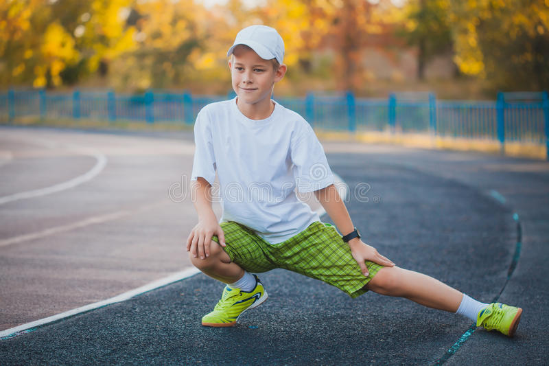 Делать мальчика предназначенный для подростков резвится тренировки на стадионе стоковое изображение