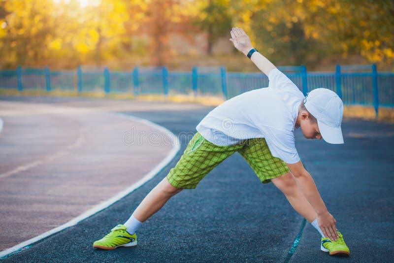 Делать мальчика предназначенный для подростков резвится тренировки на стадионе стоковое фото