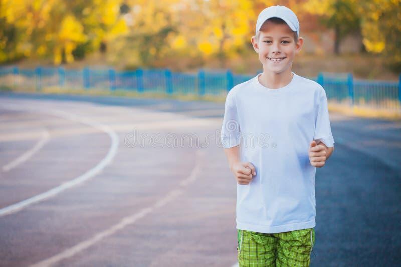 Делать мальчика предназначенный для подростков резвится тренировки на стадионе стоковые изображения
