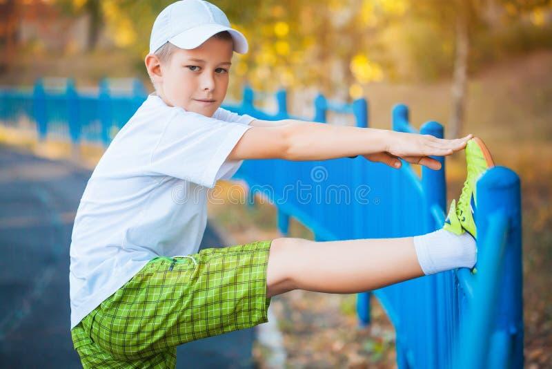 Делать мальчика предназначенный для подростков резвится тренировки на стадионе стоковая фотография rf